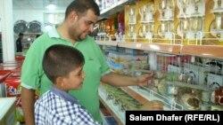 مواطن وإبنه يتسوقان في السوق التعاونية الجديدة في ميسان