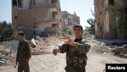 A Kurdish fighter from the People's Protection Units (YPG) gestures in Raqqa, Syria.