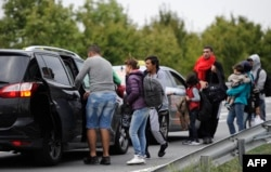 گروهی از پناهجویان در تلاش برای گرفتن تاکسی که آنها را از مجارستان به وین در اتریش برساند