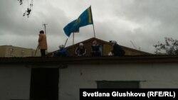 Аштық жариялаған әйелдер сүрілетін үйдің шатырына шығып алды. Астана, 15 тамыз 2014 жыл.