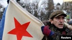 Мужчина с военным флагом советской эпохи на пророссийском митинге в Симферополе. 28 февраля 2014 года.