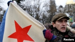 A man hold a Soviet-era military flag during a pro-Russian rally in Simferopol, Crimea, on February 28.