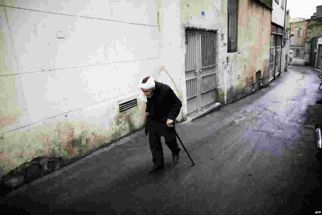 An elderly man walks down an alley south of Tehran on November 21. (AFP/Behrouz Mehri)