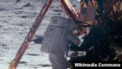 Нил Армстронг делает шаги по поверхности Луны.