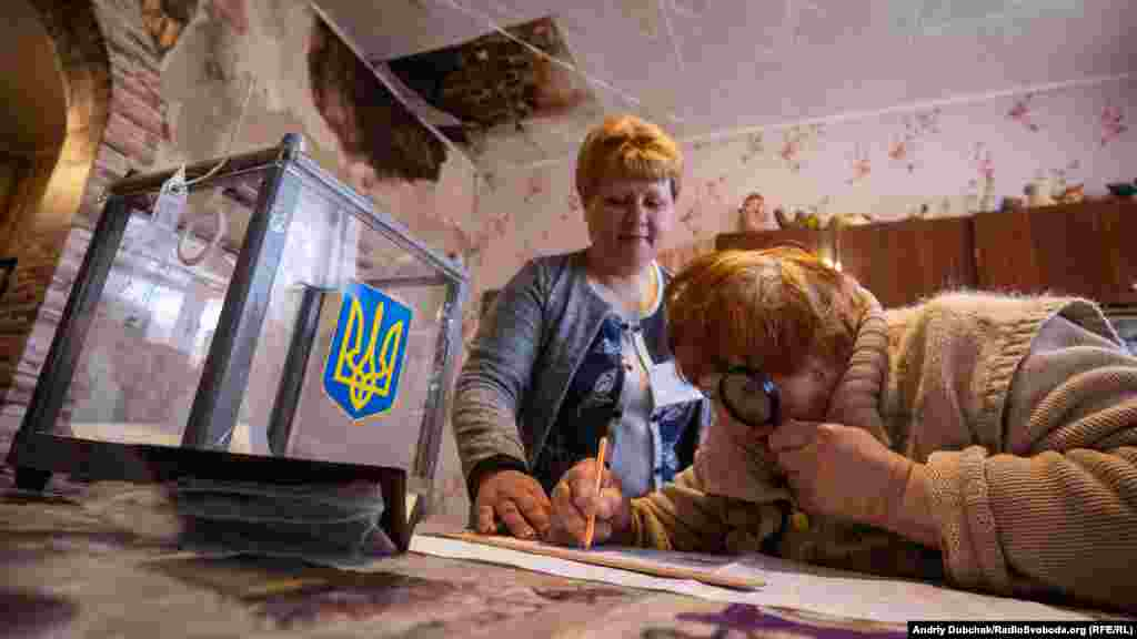 A woman inspects the ballot paper during home voting in the village of Novotroitse in the Donetsk region.