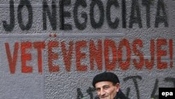 Kosovo -- An ethnic Albanian man walks next by graffiti reading 'No negotiations, Self-determination' in Pristina, 12Nov2007