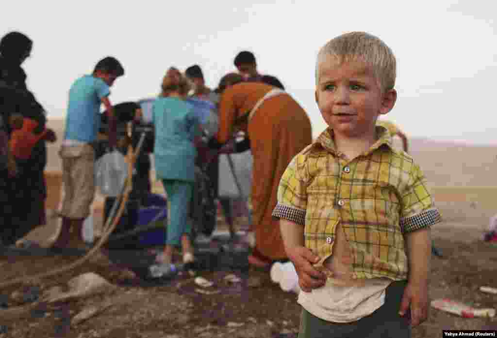 A Syrian boy stands near people using containers to collect water at the Arbat refugee camp in the northern Iraqi province of Sulaimaniyah. (Reuters/Yahya Ahmad)