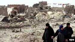 Women in Mosul walk through rubble at the site of a bomb attack in September.