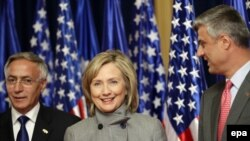 Prime Minister Hashim Thaci (right) and acting President Jakup Krasniqi welcome U.S. Secretary of State Hillary Clinton to Pristina on October 13.