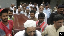 Pakistan -- People carry a coffin containing the dead body of journalist Syed Salim Shahzad at Karachi airport, 01Jun2011