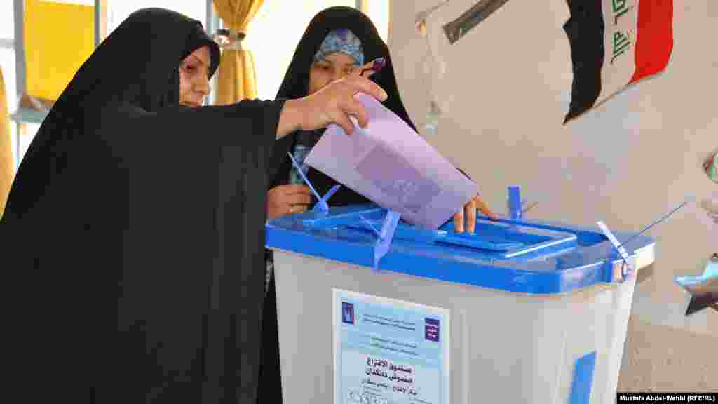 A woman casts her ballot in Karbala.
