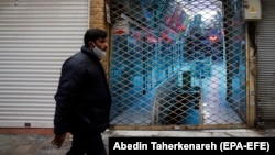 An Iranian man wearing a face mask walks past a closed shopping mall at a bazaar in Tehran earlier this year.