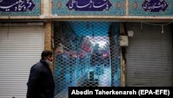 An Iranian man wearing a face mask walks past a closed shopping arcade in Tehran's Tajrish bazaar. April 10, 2020