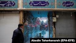 An Iranian man wearing a face mask walks past a closed shopping arcade at Tajrish bazaar, in Tehran, April 10, 2020