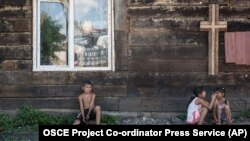 Roma children rest in the shade of a church wall inside an encampment on the outskirts of Uzhhorod in western Ukraine. (file photo)