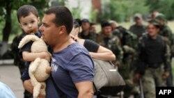 Мужчина с ребенком на руках оставляют свой дом в поисках убежища после боев между сепаратистами и украинскими военными в Луганске. 2 июня 2014 года.
