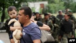 Покидающие Славянск беженцы (на переднем плане). 2 июня 2014 года.