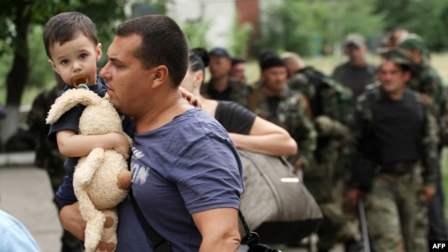 A man carries his son as he leaves his apartment building during an ongoing shoot-out between pro-Russian militants and border guards defending the Federal Border Headquarters in Luhansk on June 2.