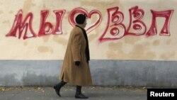 Женщина проходит мимо граффити, посвященных Путину. Москва, 7 октября 2012 года.