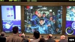 На екрані в російському Центрі управління польотами Сергій Волков на МКС у середньому ряду праворуч, фото 10 квітня 2008 року