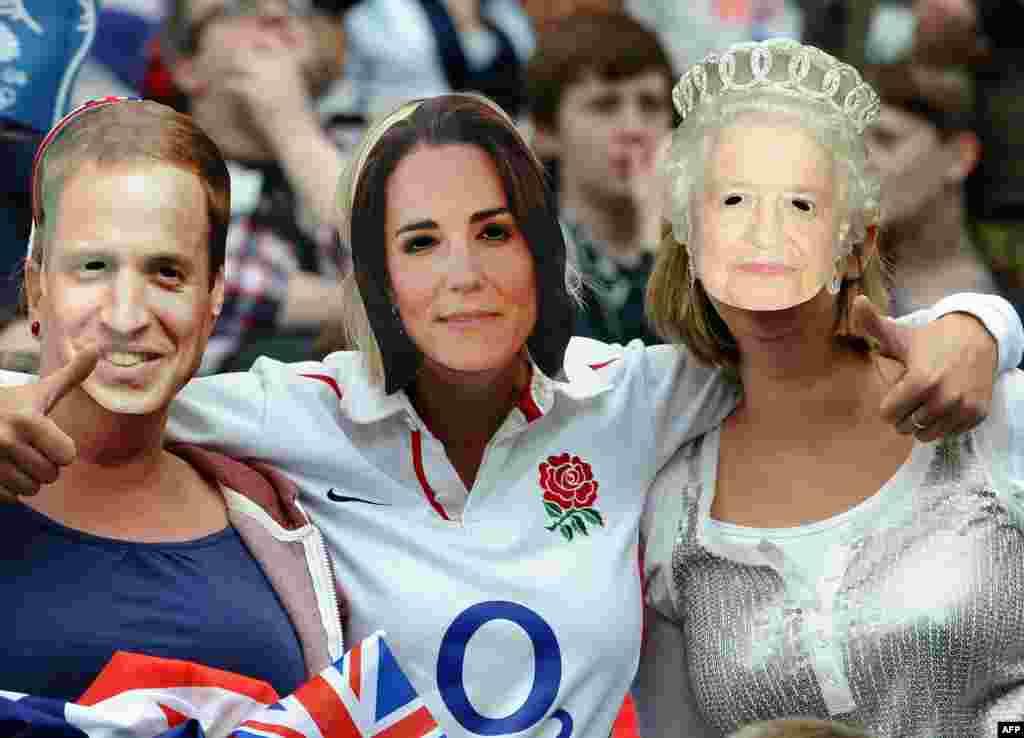 Британские фанаты в масках принца Уильяма, принцессы Кейт Мидлтон и королевы Елизаветы II на матче 1/4 финала женского турнира по футболу между Великобританией и Канадой. Маски на трибунах очень популярны: можно встретить еще и Бэкхема или Уиггинса