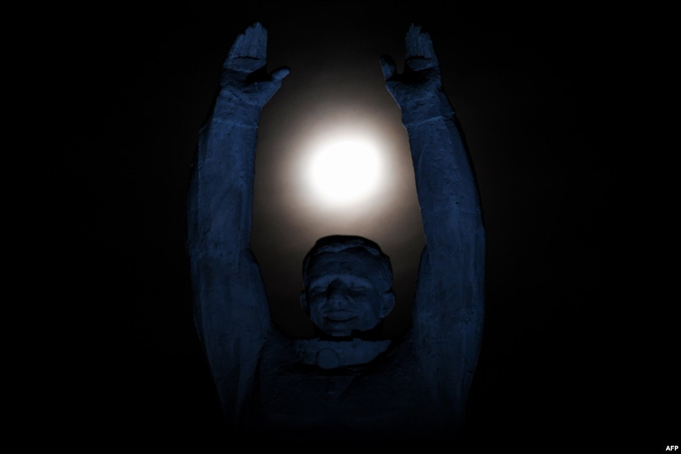 The moon is pictured over a statue of Russian cosmonaut Yury Gagarin at the Russian-leased Baikonur cosmodrome in Kazakhstan. (AFP/Kirill Kudryavtsev)