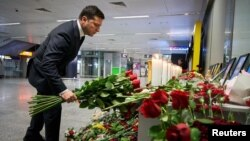 Ukrainian President Volodymyr Zelenskiy lays flowers at a memorial to the crash victims at Kyiv's Boryspil International Airport.