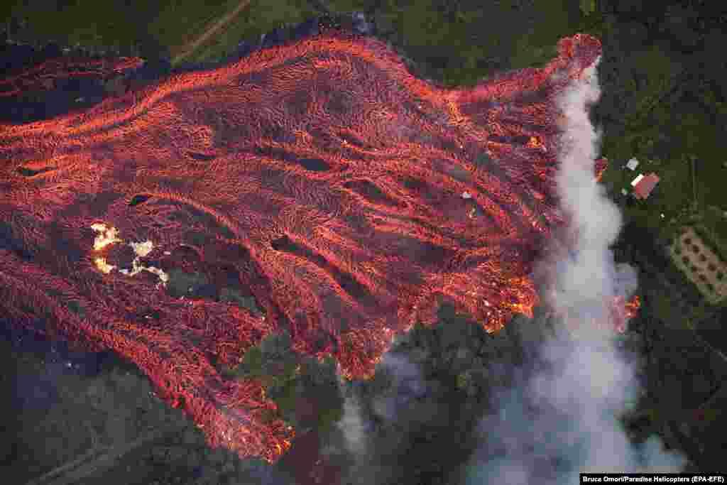 На фото видно як палає будинок, оскільки потік лави, яка швидко рухається, поглинає все на своєму шляху. Пагоа, Гаваї, 19 травня. Виверження вулкана Кілауеа в штаті Гаваї, США стало найбільшим за десятиліття, зруйнувавши понад 40 будинків і змусивши тисячі людей евакуюватися. (epa-EFE/Bruce Omori)