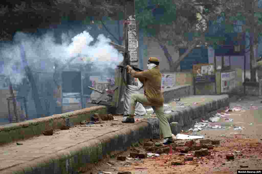 A policeman fires teargas during a protest in the Seelampur area of New Delhi on December 17.