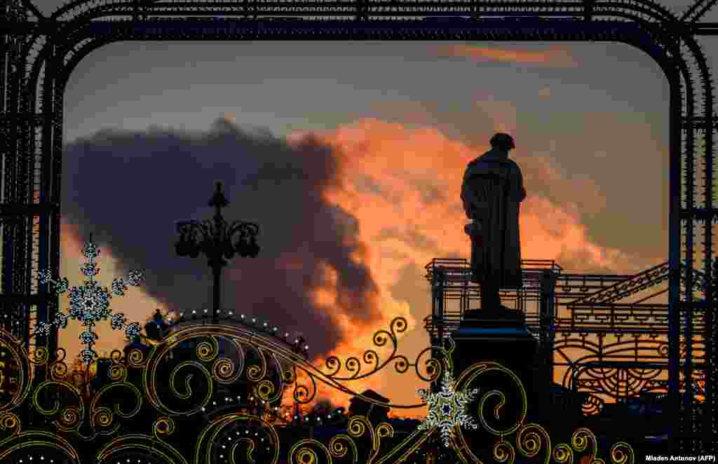 The sun brightens clouds of steam from a local power plant behind a monument to Russian poet Aleksandr Pushkin in downtown Moscow. (AFP/Mladen Antonov)