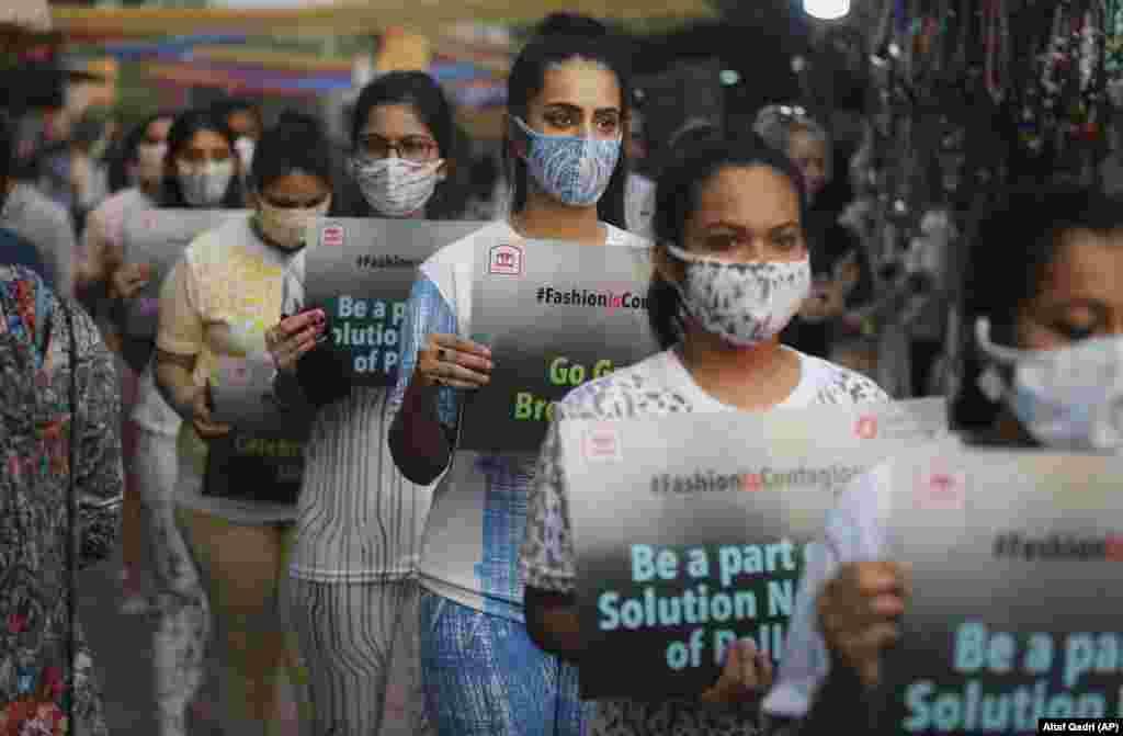 Hindi studentleri Nýu-Delide howanyň aşa hapalanmagyna ünsi çekmek üçin bazar meýdançasynyň içinden ýöriş edýärler. (AP/Altaf Qadri)