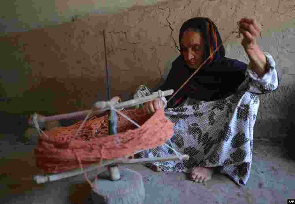 An Afghan refugee prepares thread for carpet weaving at the Khorasan refugee camp near Peshawar. (AFP/A. Majeed)