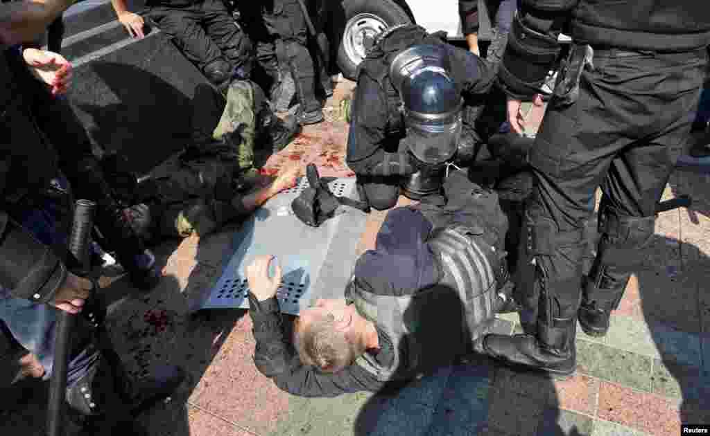 При столкновениях в августе 2015 году у здание Верховной Рады в Киеве офицеры национальной гвардии совместно с полицейскими помогают раненым