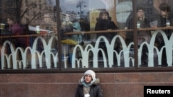 A man begs for money outside a McDonald's restaurant in central Kyiv, Ukraine. (Reuters/Gleb Garanich)