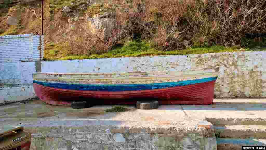 Деревянная лодка в цветах российского флага в Симеизе