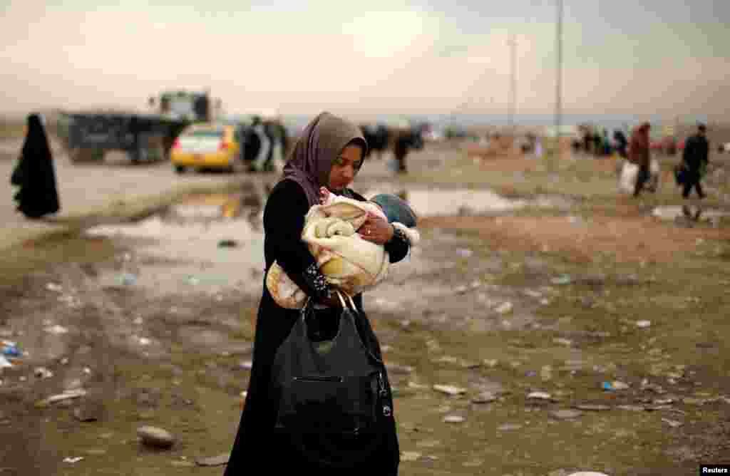 A displaced Iraqi woman carries her baby after fleeing the battle between Iraqi rapid-response forces and Islamic State militants near Mosul. (Reuters/Ahmed Jadallah)