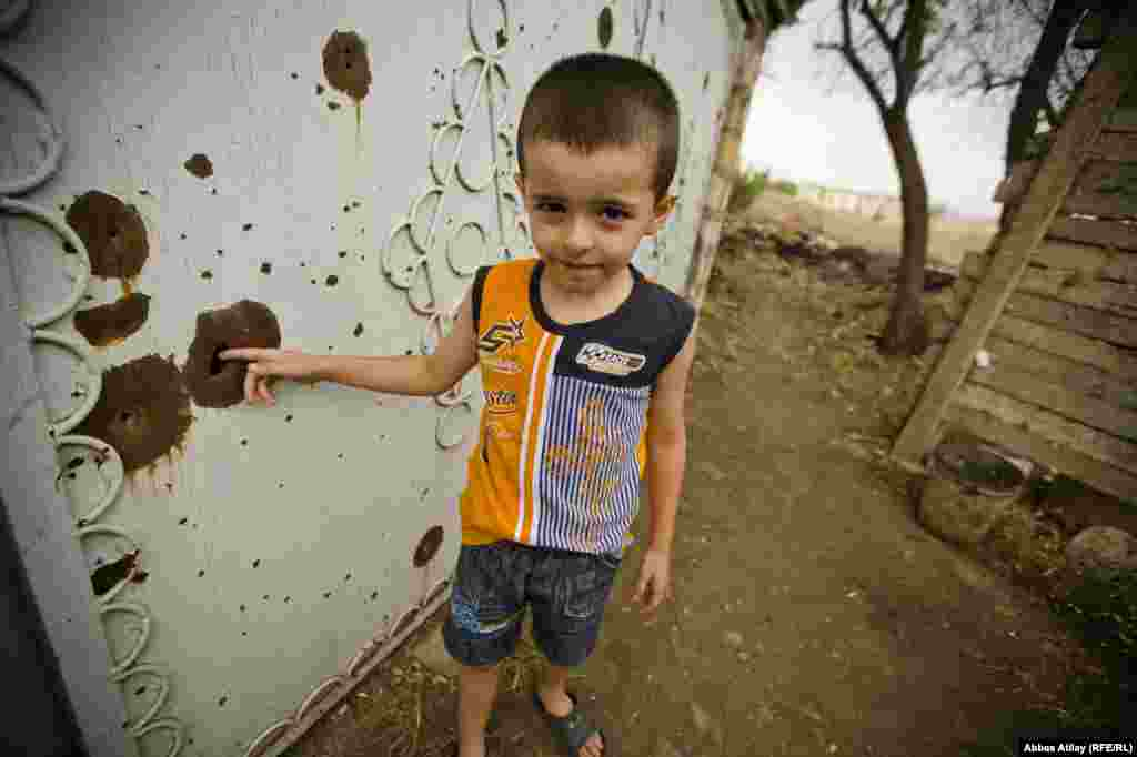 Siyavus has two boys. One stands at the bullet-riddled door on his property.