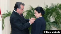 Президент Таджикистана Эмомали Рахмон вешает орден на грудь своей дочери Озоды Рахмон. 28 августа 2015 года