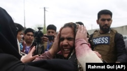 FILE: Family members cry after an attack on a Sikh Gudwara in the capital Kabul on March 25.