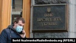 Чоловік у захисній масці поруч із Офісом президента України
