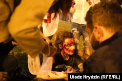 A wounded protester is tended to while awaiting an ambulance.