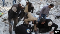 Syrian volunteers search for victims amid the rubble of buildings destroyed by air strikes in Syria's Idlib Province this week.