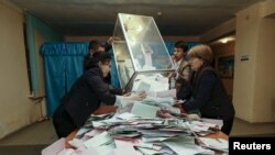 Члены избирательной комиссии на участке в Кызылорде достают из избирательной урны бюллетени. 20 марта 2016 года.