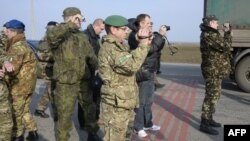 OSCE military observers take photos during negotiations with pro-Russian forces at a checkpoint blocking the entrance to Crimea last month.