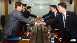 North and South Korean delegates shake hands during a meeting at the Kaesong industrial complex on September 11.