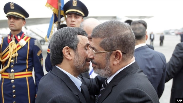 Deposed Egyptian President Muhammad Morsi (right) greets Iranian President Mahmud Ahmadinejad in Cairo in February.