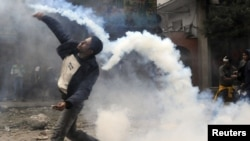 Протестующий на площади Тахрир бросат слезотачивый газ, брошенный силами безопасности. Каир, 20 ноября 2011 года.
