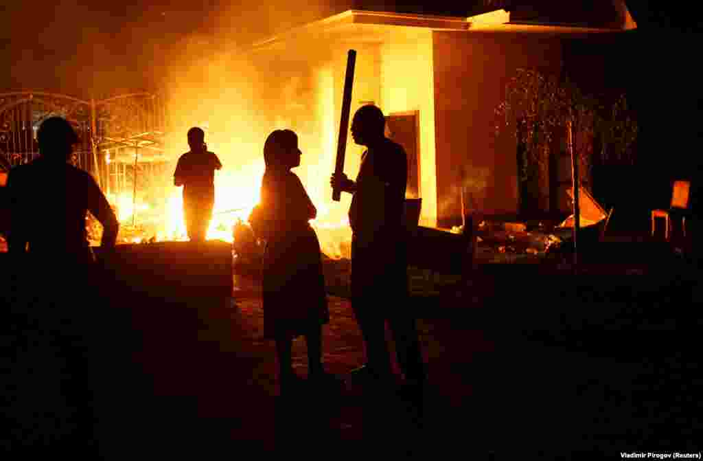 A fire rages in the compound as supporters of the ex-president arm themselves with sticks.