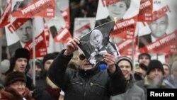 Лідер «Лівого фронту» Сергій Удальцов спалює портрет Володимира Путіна під час протестного маршу у Москві, 13 січня 2013 року