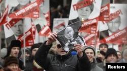 Лидер оппозиционного движения «Левый фронт» Сергей Удальцов сжигает фотографию Путина во время марша против «закона Димы Яковлева». Москва, 13 января 2013 года.